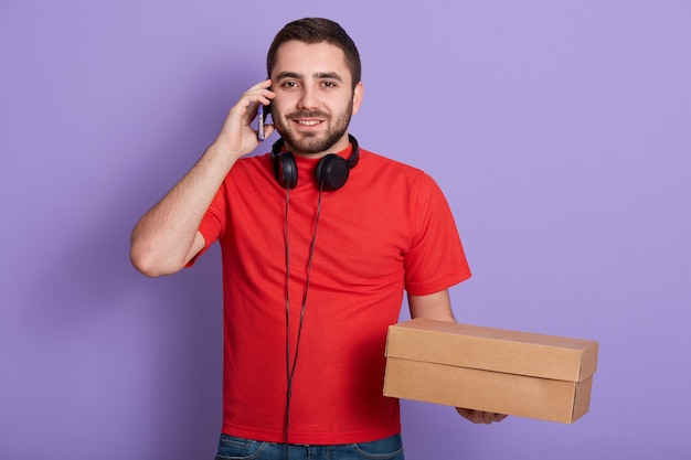 Portrait of smiling bearded delivery man wearing red casual t-shirt, talking via mobile phone while holding blank carton box isolated over lilac, posing with headphones around neck.