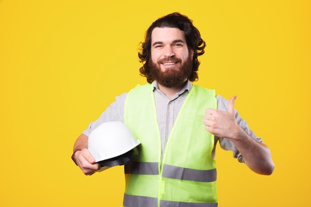 Portrait of smiling bearded engineer holding white helmet and showing thumb up