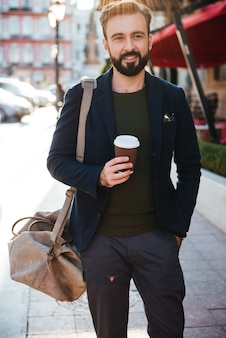 Portrait of a smiling bearded man drinking coffee