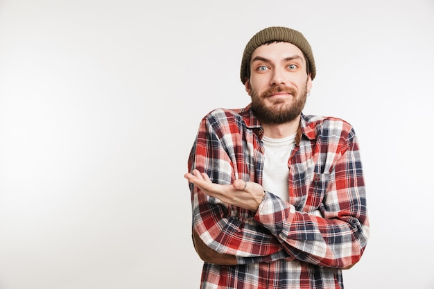 Portrait of a smiling bearded man in plaid shirt pointing away