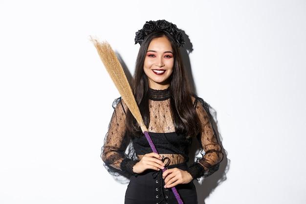 Ritratto di bella donna asiatica sorridente in costume da strega che tiene scopa e guardando felice a porte chiuse, celebrando halloween, godendo di dolcetto o scherzetto, sfondo bianco.