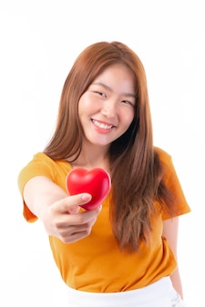 Portrait of smiling a beautiful asian young woman holding red heart in hand on white background- valentine day concept