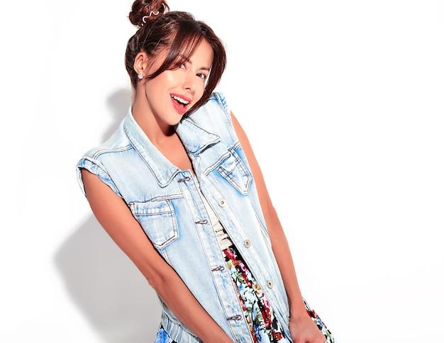 Il ritratto di bello modello sveglio sorridente della donna del brunette in jeans casuali dell'estate copre senza trucco con l'acconciatura dei corni isolata su bianco