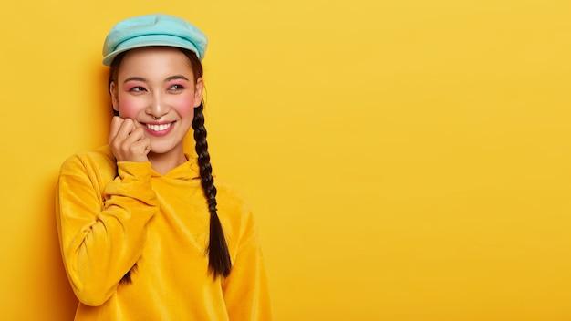 Ritratto di sorridente bella ragazza dai capelli scuri con due trecce, ha un trucco rosa brillante, indossa un cappello elegante e un maglione di velluto a coste con cappuccio