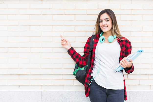 Portrait of a smiling beautiful female student holding books and carrying backpack on shoulder pointing her finger against white brick wall