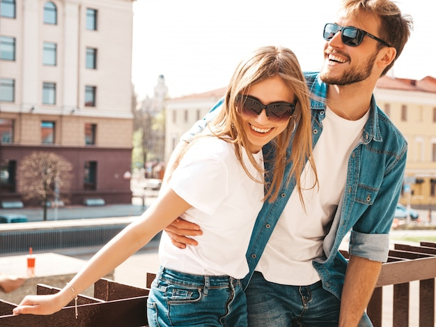 Portrait of smiling beautiful girl and her handsome boyfriend in casual summer clothes and sunglasses.  . hugging