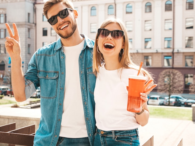 Portrait of smiling beautiful girl and her handsome boyfriend in casual summer clothes.   . with bottle of water and straw