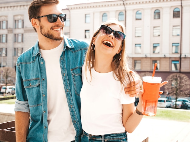 Portrait of smiling beautiful girl and her handsome boyfriend in casual summer clothes.   . woman with bottle of water and straw
