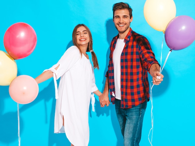 Portrait of smiling beautiful girl and her handsome boyfriend holding bunch of colorful balloons and laughing. happy birthday