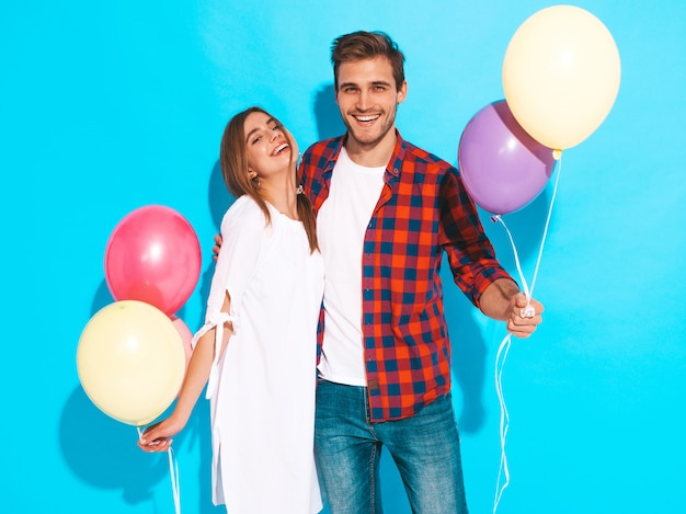 Portrait of smiling beautiful girl and her handsome boyfriend holding bunch of colorful balloons and laughing. happy couple. happy birthday