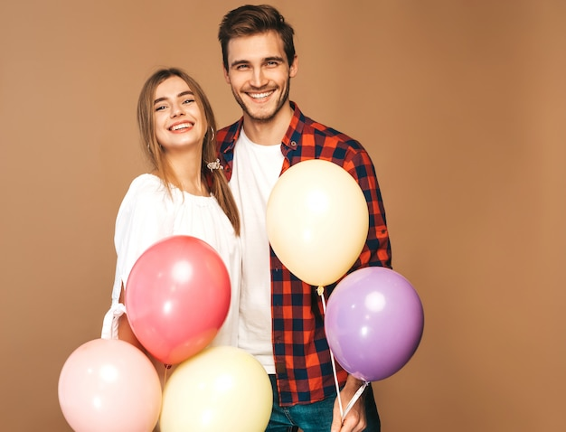 Portrait of smiling beautiful girl and her handsome boyfriend holding bunch of colorful balloons and laughing. happy couple in love. happy birthday