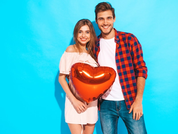 Portrait of smiling beautiful girl and her handsome boyfriend holding heart shaped balloons and laughing. happy couple in love. happy valentine's day. posing