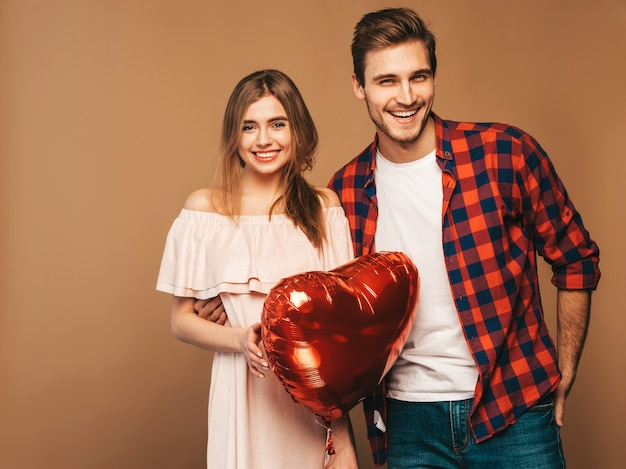 Portrait of smiling beautiful girl and her handsome boyfriend holding heart shaped balloons and laughing. happy couple in love. happy valentine's day.
