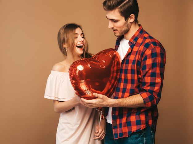 Portrait of smiling beautiful girl and her handsome boyfriend holding heart shaped balloons and laughing. happy couple in love. happy valentine's day