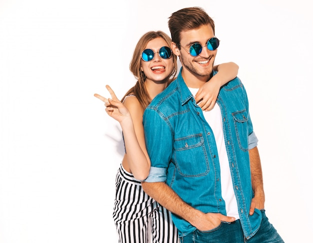 Portrait of smiling beautiful girl and her handsome boyfriend laughing.happy cheerful couple in sunglasses. and showing peace sign