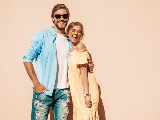 Ritratto di bella ragazza sorridente e il suo bel ragazzo. donna in abito estivo casual e uomo in jeans. famiglia felice e allegra. femmina divertirsi in strada vicino al muro