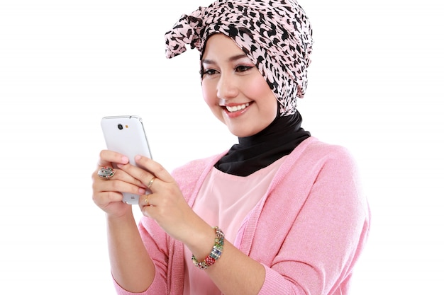 Portrait of a smiling beautiful muslim woman texting with her smartphone