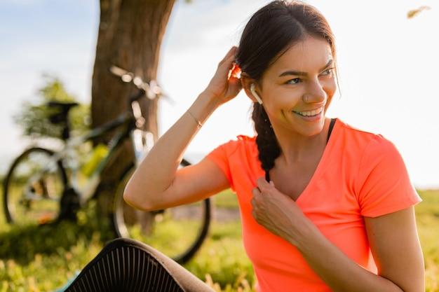 Ritratto di bella donna sorridente che fa sport mattina nel parco