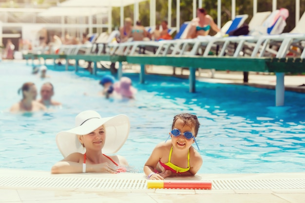 Portrait of smiling beautiful woman and her little cute daughter in sunglasses in pool outdoor