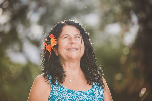 Portrait of smiling beautiful woman in nature with flower on her hair