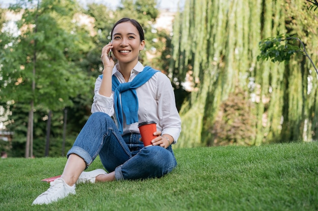 Portrait of smiling beautiful woman talking on mobile phone, sitting on grass