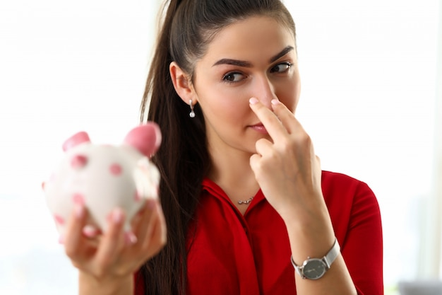 Portrait of smiling beautiful woman watching over bad and guilty piggybank