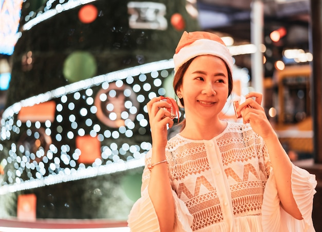 Portrait of smiling beautiful young asian woman with gift on the festive christmas fair