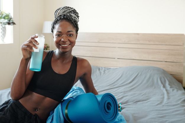 Portrait of smiling beautiful young black woman with braided hair resting on bed and drinking vitamin water after working out at home