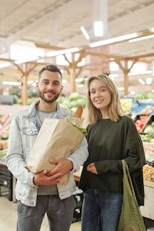 Portrait of smiling beautiful young couple in casual outfits standing with bags at modern farmers market