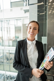 Portrait of smiling beautiful young woman in jacket holding graph papers and standing in office elevator