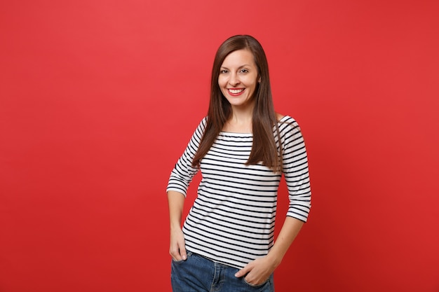 Portrait of smiling beautiful young woman in striped clothes standing, holding hands in pockets