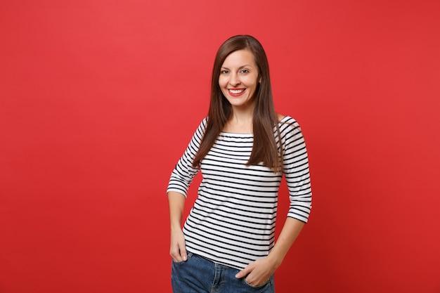 Ritratto di bella giovane donna sorridente in abiti a righe in piedi, tenendosi per mano in tasca