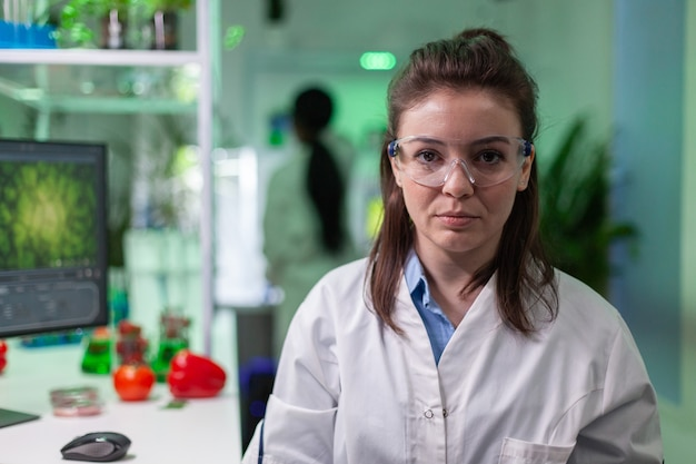 Portrait of smiling biologist woman analyzing genetically modified organism