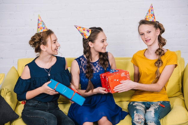 Portrait of smiling birthday girl taking presents from friends
