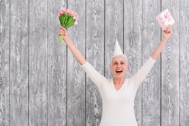 Portrait of smiling birthday woman holding flower bouquet with gift box in front of wooden background