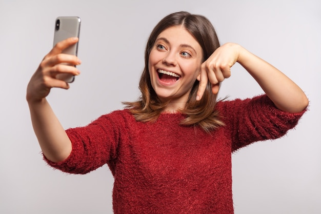 Portrait of smiling blogger girl in sweater making video call via mobile phone and pointing down