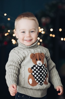 Portrait of a smiling blond baby in warm turtle neck sweater with teddy bear looking at camera.