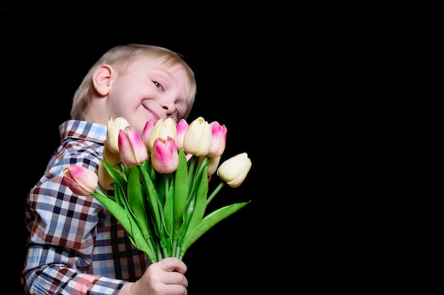 Portrait smiling blond boy with a bouquet of tulips for mothers day