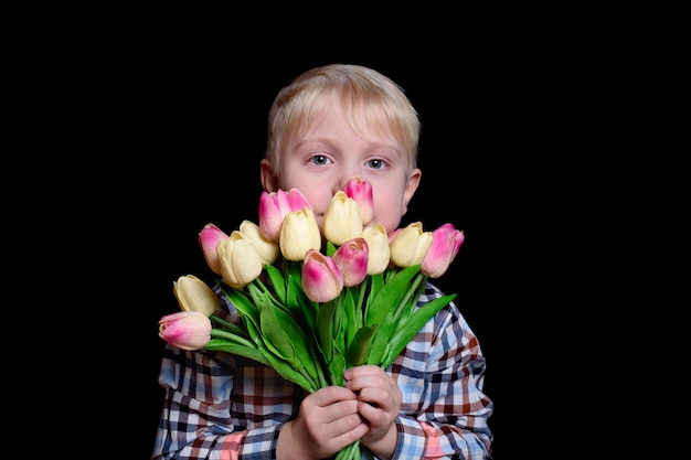 Portrait smiling blond boy with a bouquet of tulips.