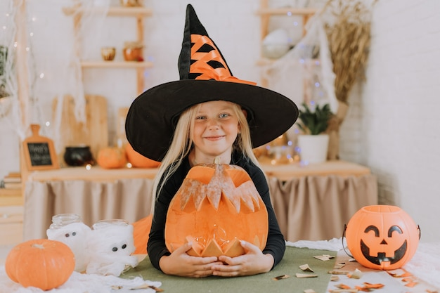 Portrait a smiling blonde girl of european appearance in huge witch hat hugs a large pumpkin lantern