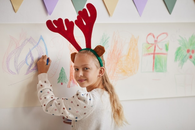 Portrait of smiling blonde girl wearing antlers drawing christmas pictures on wall during art class, copy space
