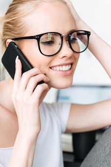 Portrait of smiling blonde lady talking on smartphone
