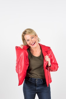 Portrait of smiling blonde mature woman in red jacket standing against white background