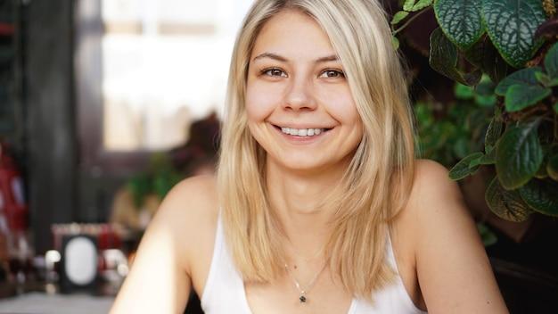 Portrait of smiling blonde sitting near green plants