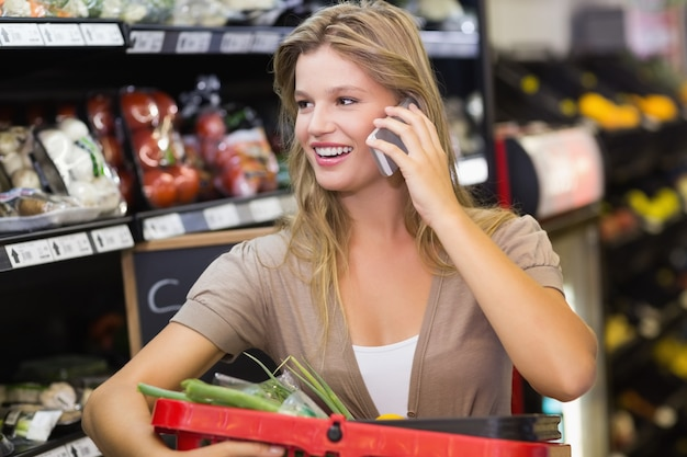 Portrait of smiling blonde woman buying vegetables and phoning