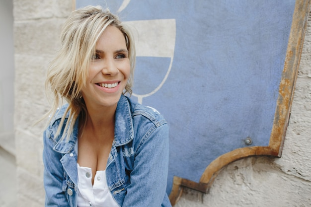Portrait of a smiling blonde woman in a denim jacket