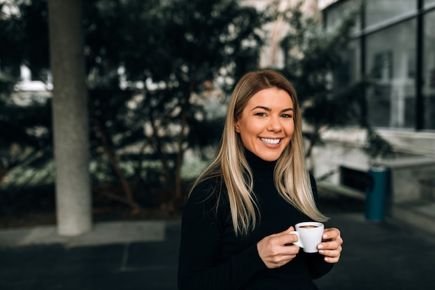 Portrait of a smiling blonde woman holding a cup of coffee. looking at camera.