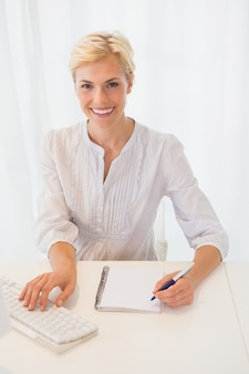 Portrait smiling blonde woman using computer