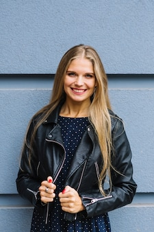 Portrait of a smiling blonde young woman in black jacket standing against wall