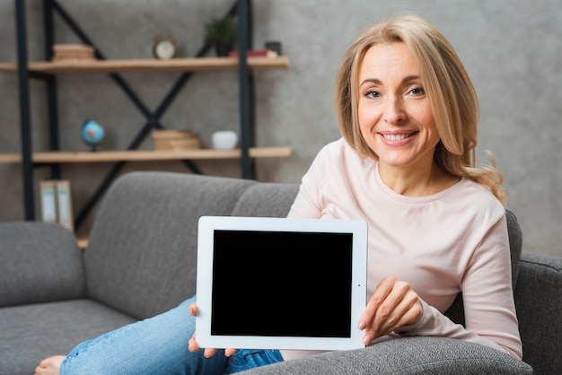 Portrait of a smiling blonde young woman showing digital tablet screen